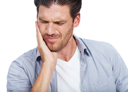 Man with pain from broken tooth caused by irregularly spaced teeth